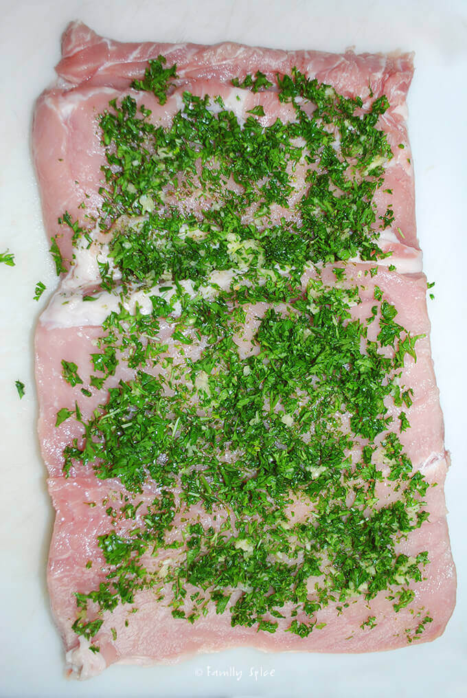 Herbs spread over pork for Grilled Rosemary Garlic Pork Roast by FamilySpice.com