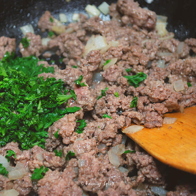 Adding parsley to make Persian Stuffed Grape Leaves: Beef and Pomegranate Dolmeh by FamilySpice.com