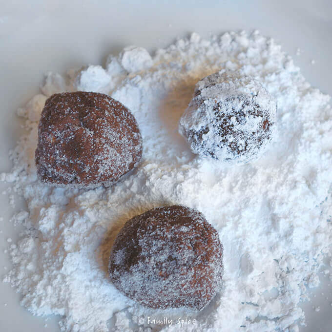 Rolling Almond Crackle Cookie dough into powdered sugar by FamilySpice.com