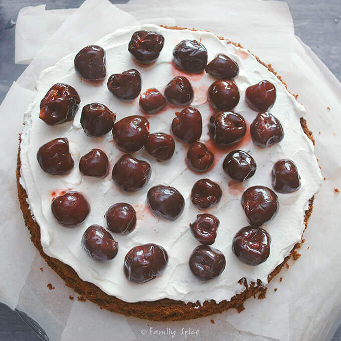 Adding liqueur soaked cherries to Black Forest Cake by FamilySpice.com