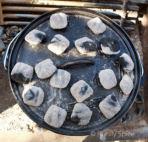 Hot coals on a Dutch Oven to learn How to Cook in a Dutch Oven - by FamilySpice.com