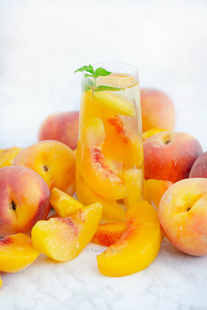 A glass of sparkling peach sangria by FamilySpice.com