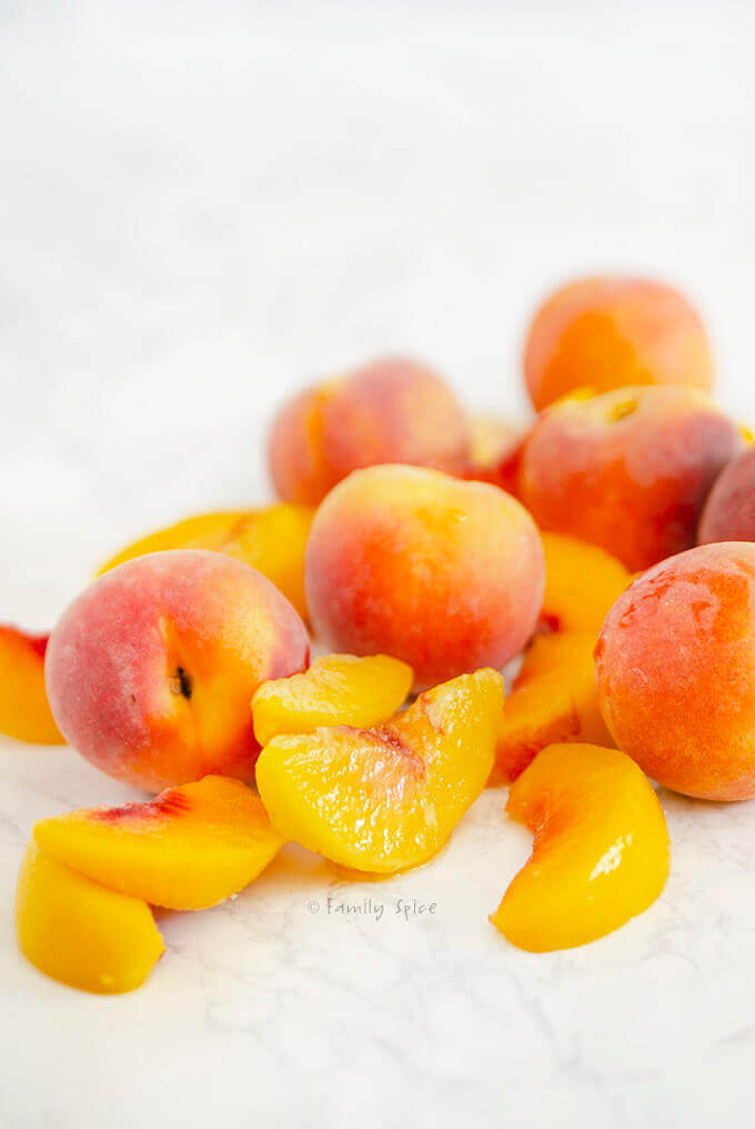 A pile of fresh whole peaches surrounded by juicy slices of peaches by FamilySpice.com