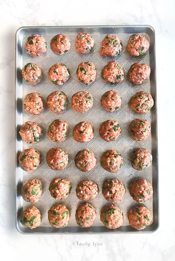 A baking sheet filled with assembled meatballs ready to bake by FamilySpice.com