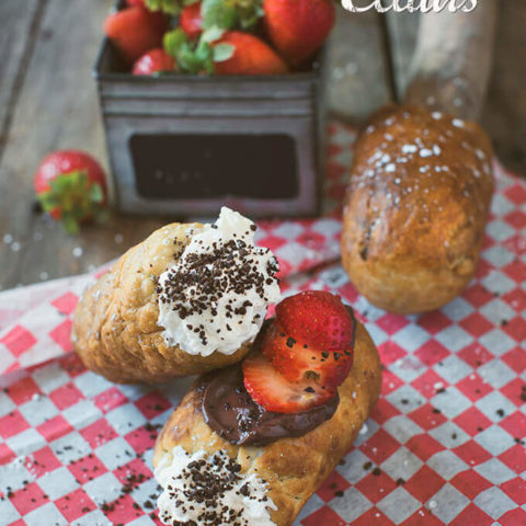 Campfire Eclairs stuffed with whipped cream, topped with chocolate pudding and strawberry slices
