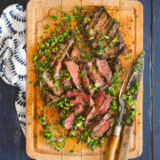 Overhead view of grilled flat iron steaks sliced with a cutting board sauce by FamilySpice.com