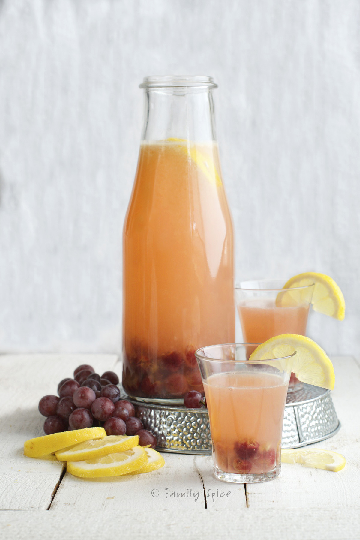 A large glass carafe of roasted grape lemonade with fresh grapes and lemons around it