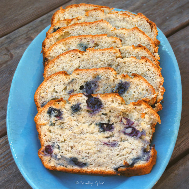An oval blue plate with banana blueberry bread slices on it