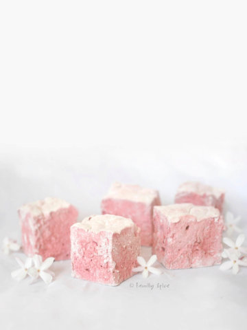 Light pink pomegranate marshmallow cubes on white background with little white flowers