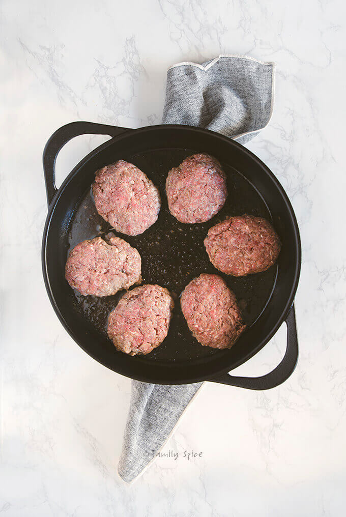 Salisbury steak meat patties browning in a large cast iron pan