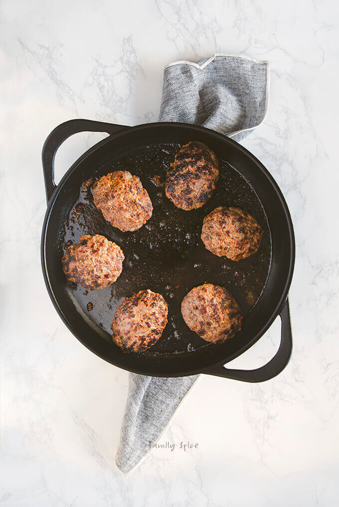 Salisbury steak meat patties cooking in a large cast iron pan