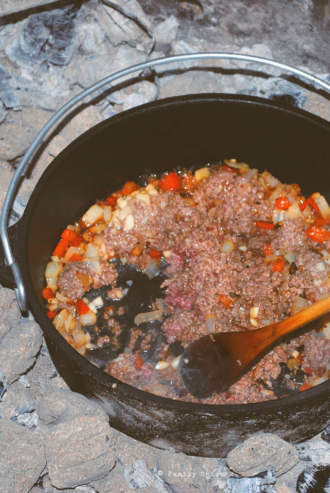 Browning meat to make Dutch oven chili in the campfire by FamilySpice.com