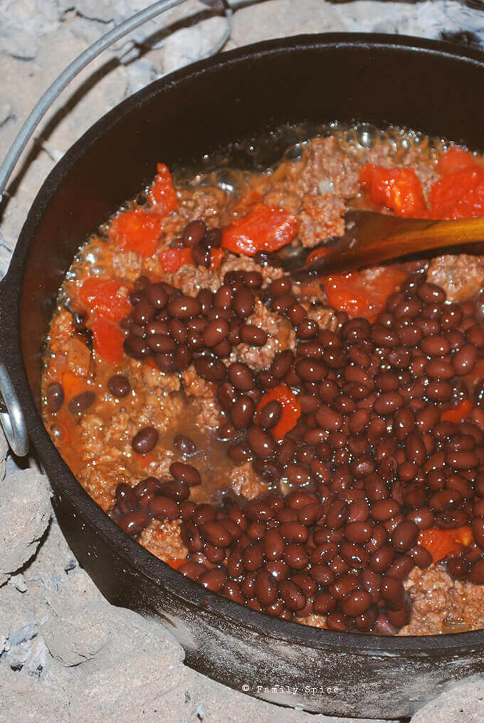 Adding beans to make Dutch oven chili by FamilySpice.com