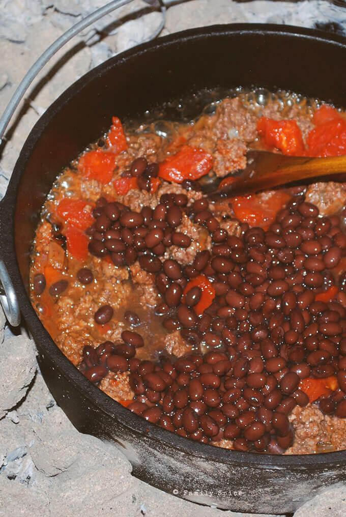 Adding beans to make Dutch oven chili by FamilySpice.com