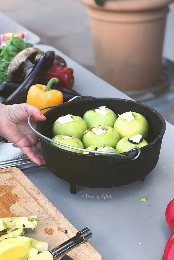 Overhead shot of apples stuffed with nuts and raisins, topped with butter and ready to be baked in the campfire in a cast iron Dutch oven by FamilySpice.com