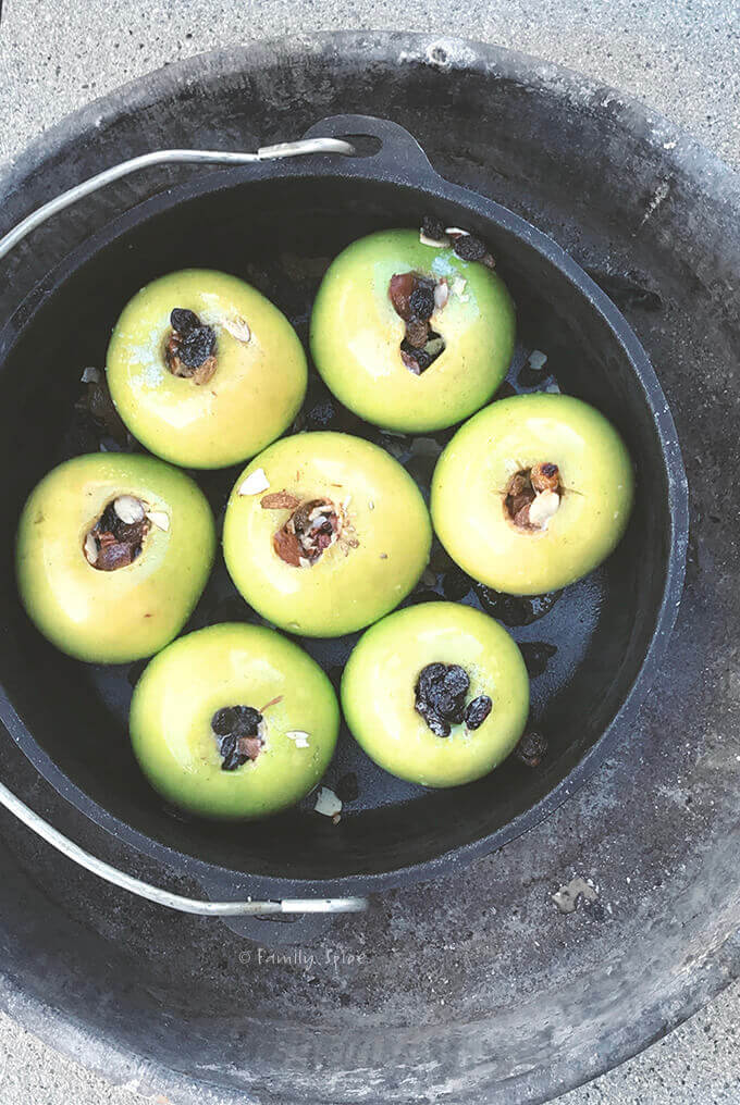 Apples stuffed with nuts and raisins ready to be baked in the campfire in a cast iron Dutch oven by FamilySpice.com