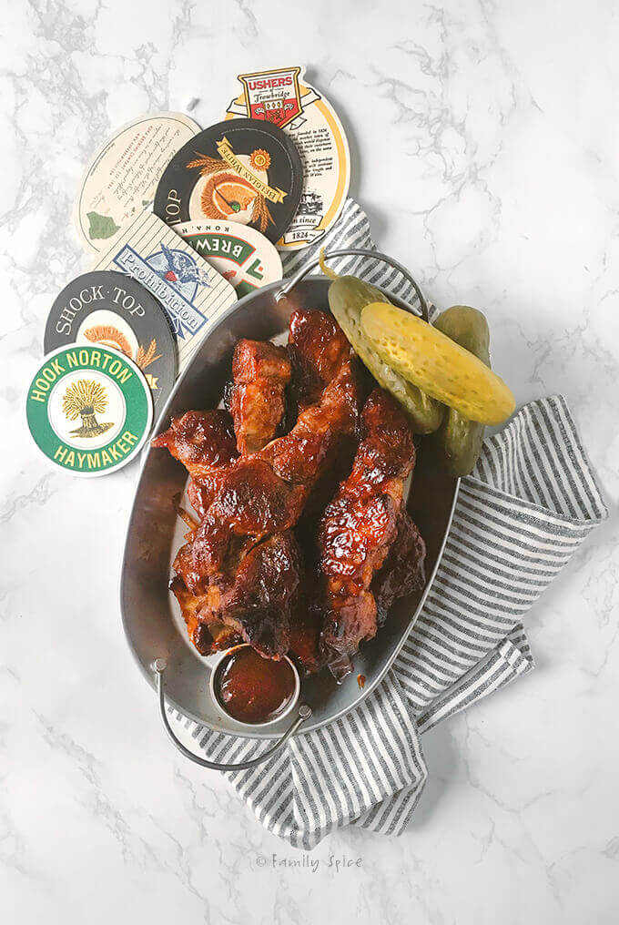 Overhead shot of an oval metal tray with pork country style ribs covered in sauce with pickles and beer coasters by FamilySpice.com