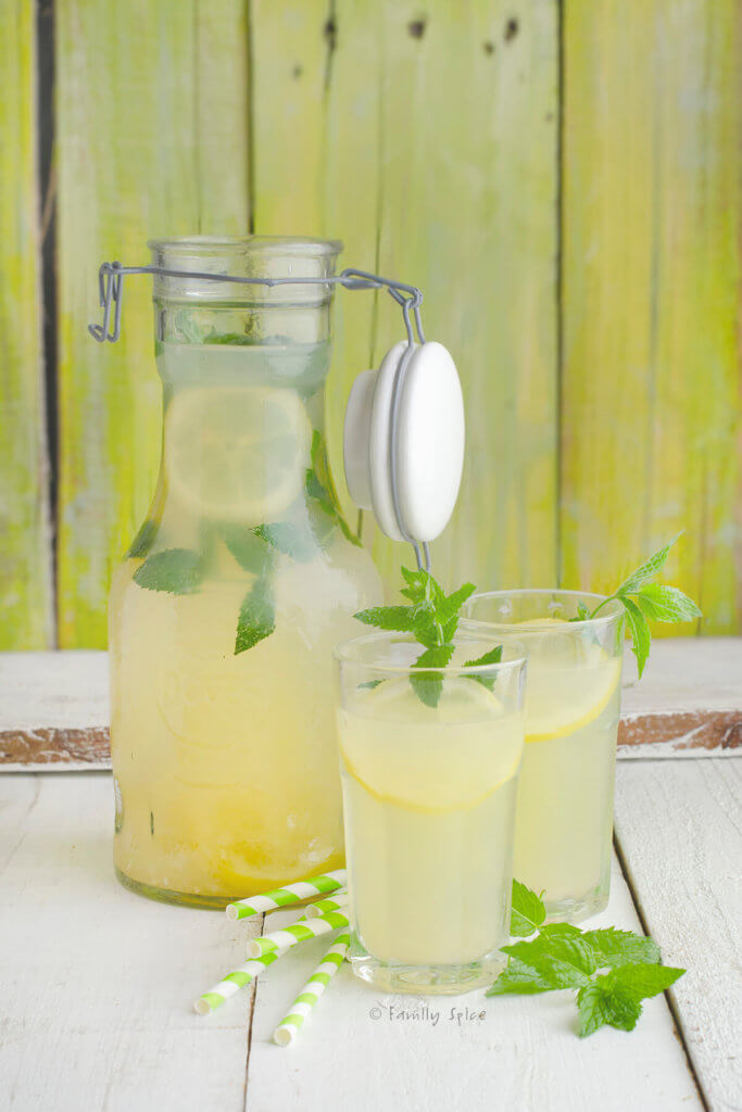 A glass bottle and two glasses of honey lemonade garnished with mint with straws next to it