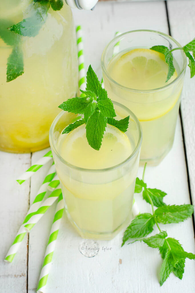Closeup of two glasses of honey lemonade garnished with mint with straws and a pitcher of lemonade next to it
