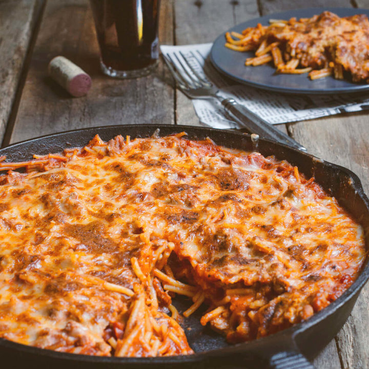 Side view of a cast iron skillet with baked spaghetti and meat sauce and slice cut out