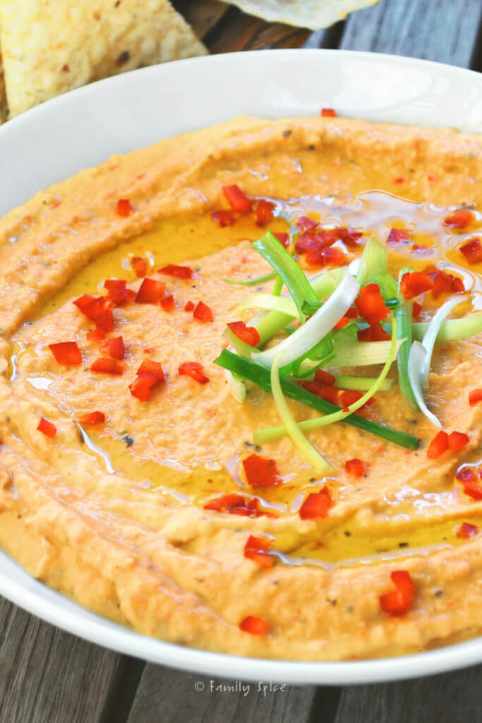 Closeup of red pepper hummus garnished with green onions, chopped red pepper and olive oil