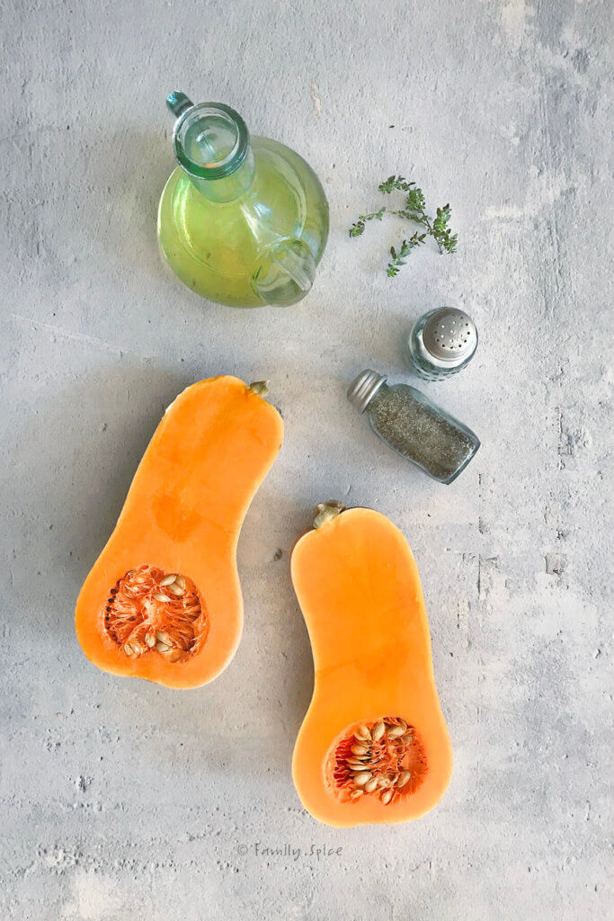 Butternut squash cut in half lengthwise with a bottle of olive oil, salt and pepper shakers and fresh thyme