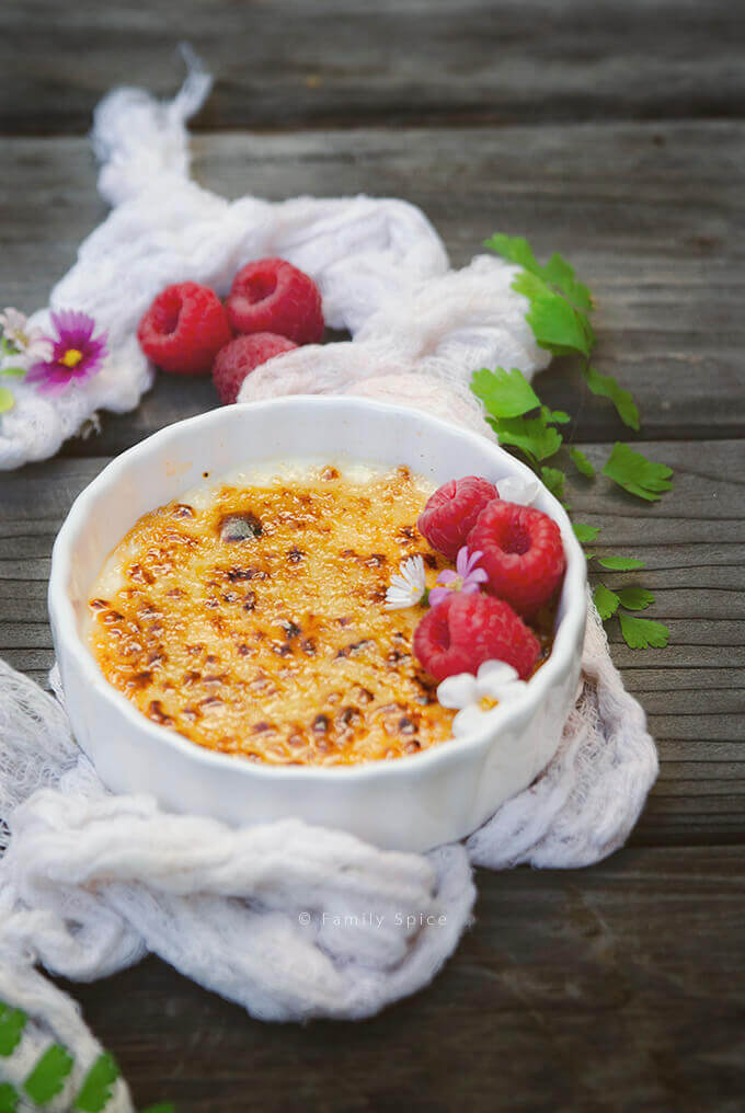 Ina Garten creme brulee garnished with flowers and fresh raspberries by FamilySpice.com