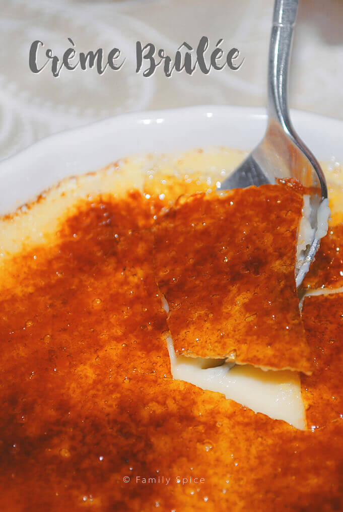 A spoon cracking the hard sugar on top of Barefoot Contessa creme brulee by FamilySpice.com