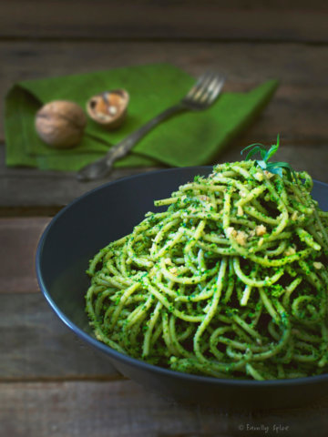 A dark bowl with spaghetti covered in kale pesto