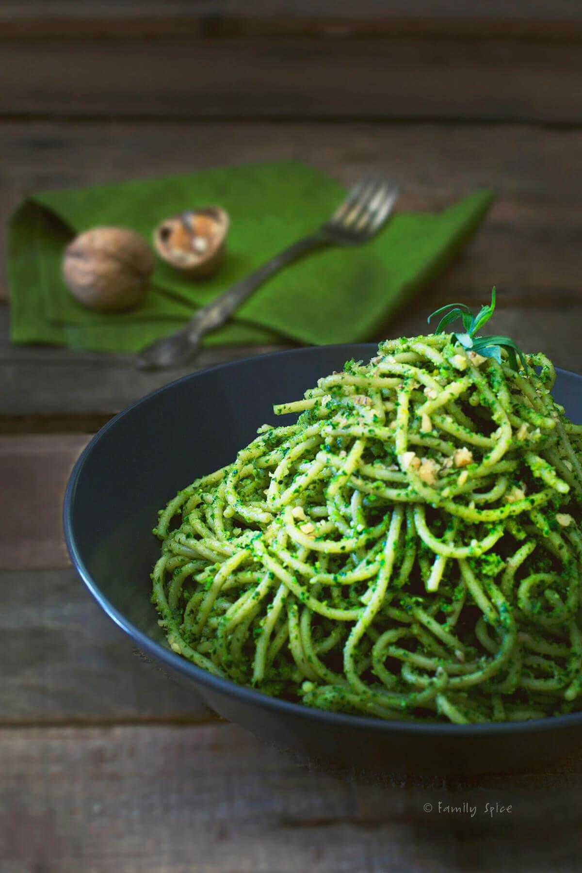 A dark bowl with spaghetti covered in kale pesto