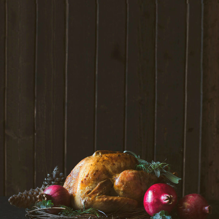 Roast turkey surrounded with pomegranates and eucalyptus branches on a dark and moody background
