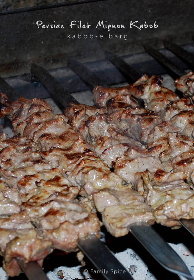 Close up of kabob barg on skewers getting grilled over hot coals by FamilySpice.com