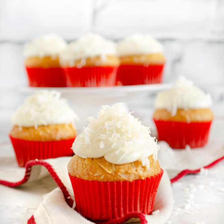 An assortment of coconut cupcakes topped with coconut in red cupcake liners