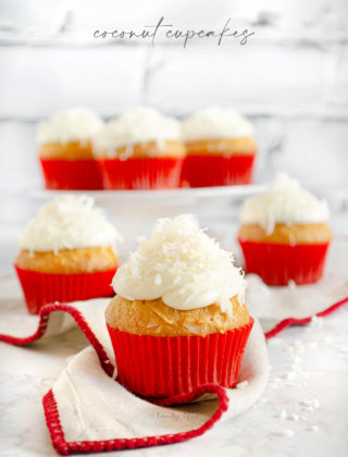 Close up of a coconut cupcake with more cupcakes behind it by FamilySpice.com