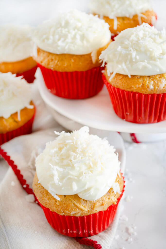 Closeup of several coconut cupcakes topped with coconut in red cupcake liners