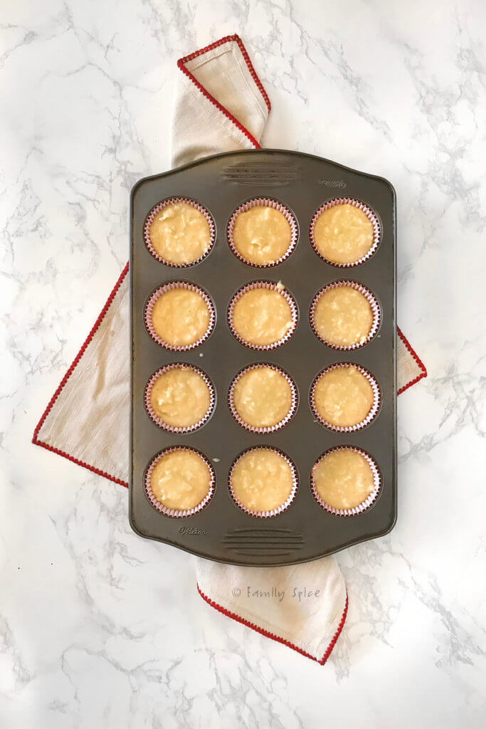 Overhead view of a cupcake pan filled with coconut cupcake batter