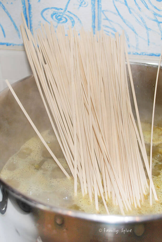 Adding noodles while cooking up Persian ashe reshteh by FamilySpice.com