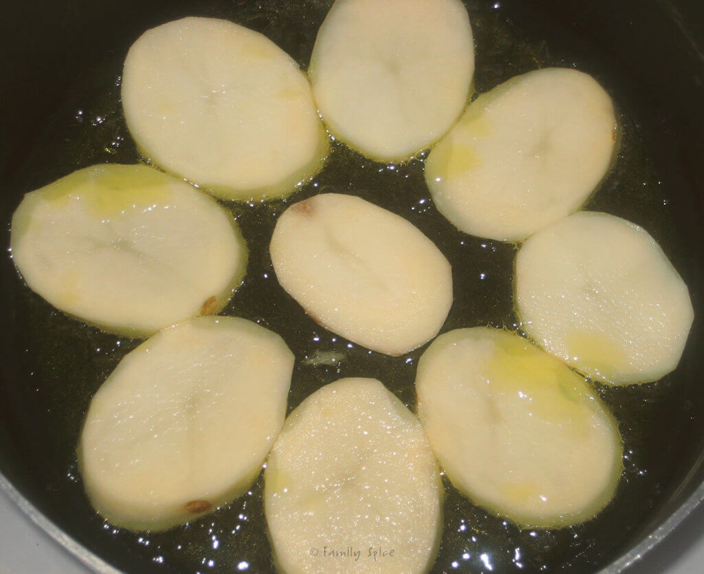 Potato slices frying in oil in a nonstick pot