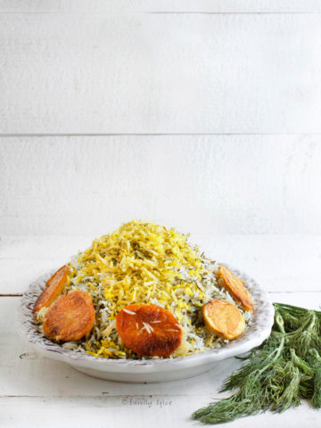 Side view of an oval platter with sabzi pollo (Persian herb rice) topped with saffron rice and surrounded with crispy potato rounds