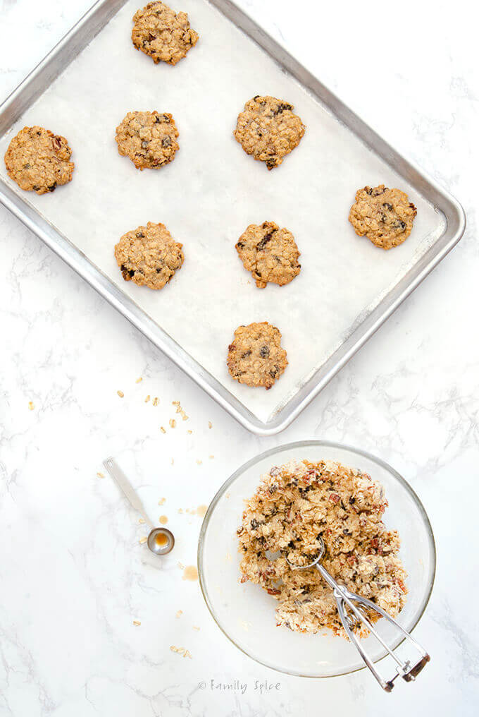 Batter in a mixing bowl plus Ina Garten Oatmeal Raisin Cookies on a baking sheet by FamilySpice.com