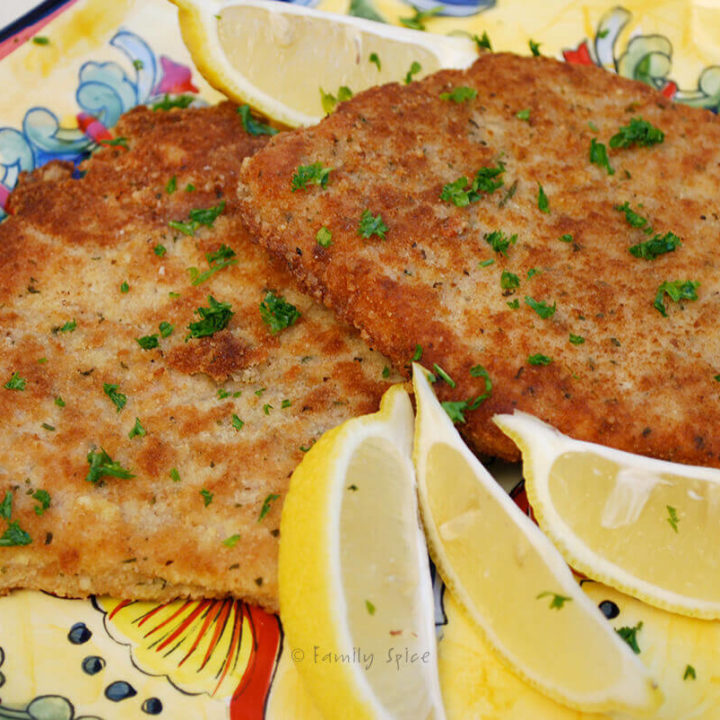 Two cutlets of pork Milanese on a yellow platter with lemon wedges