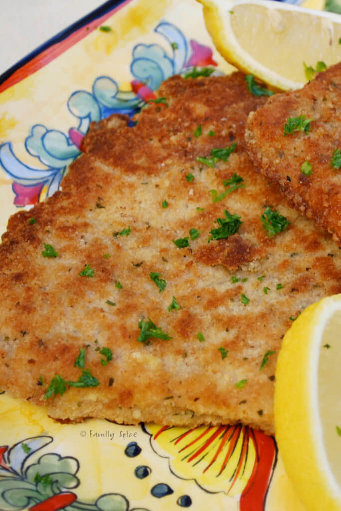 Closeup of a cutlet of pork Milanese on a yellow platter