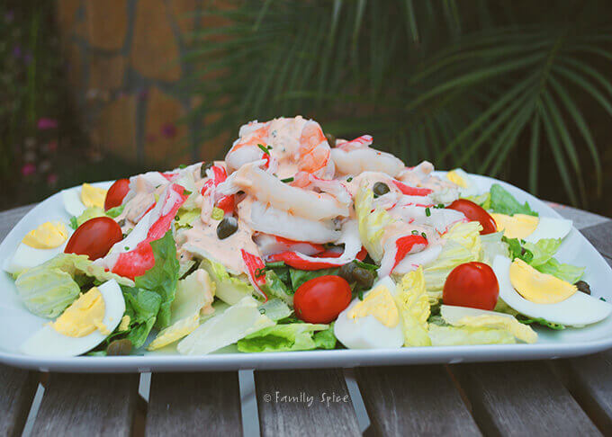 Side view of a plate filled with shrimp and crab Louie salad by FamilySpice.com