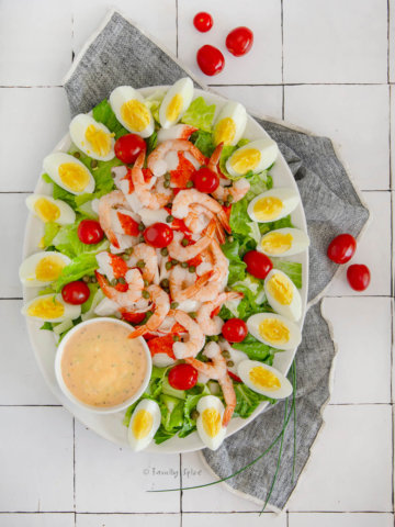Top view of an oval platter with shrimp and crab louie salad arranged neatly and a bowl of louie dressing next to it