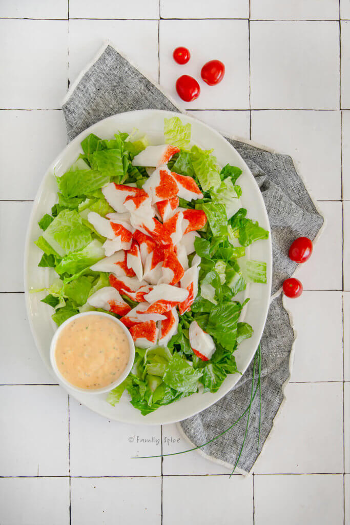 An oval platter with chopped romaine lettuce topped with imitation crab with a side bowl of louie dressing