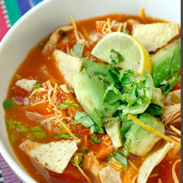 A bowl of chicken tortilla soup garnished with tortilla chips, cilantro and avocado