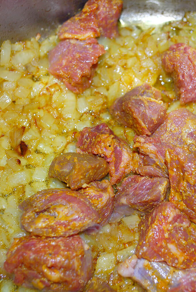 Frying up onions and stew meat for Persian Eggplant Stew (khoreshteh qiemeh bademjoon) by FamilySpice.com