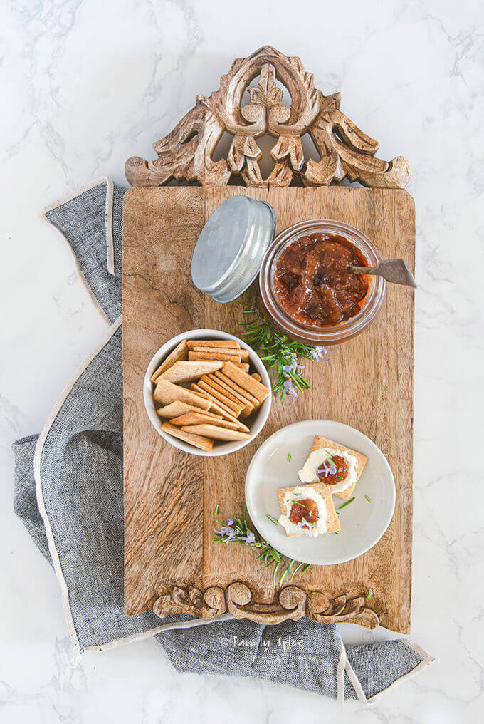 A wooden cutting board with an open jar of fig jam, crackers, cheese and rosemary by FamilySpice.com