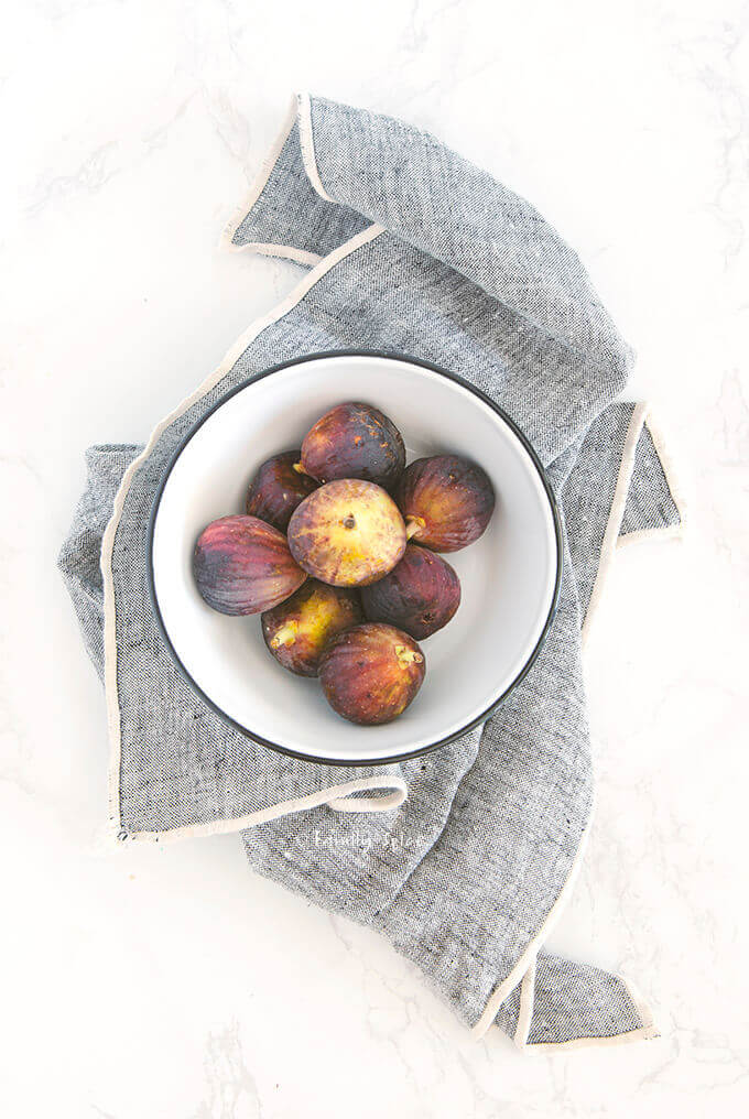Overhead view of brown turkey figs in a white enamel bowl by FamilySpice.com