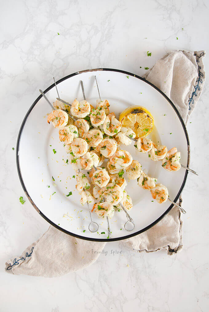 Overhead shot of platter full of Ina Garten Grilled Herb Shrimp Kabob on skewers by FamilySpice.com